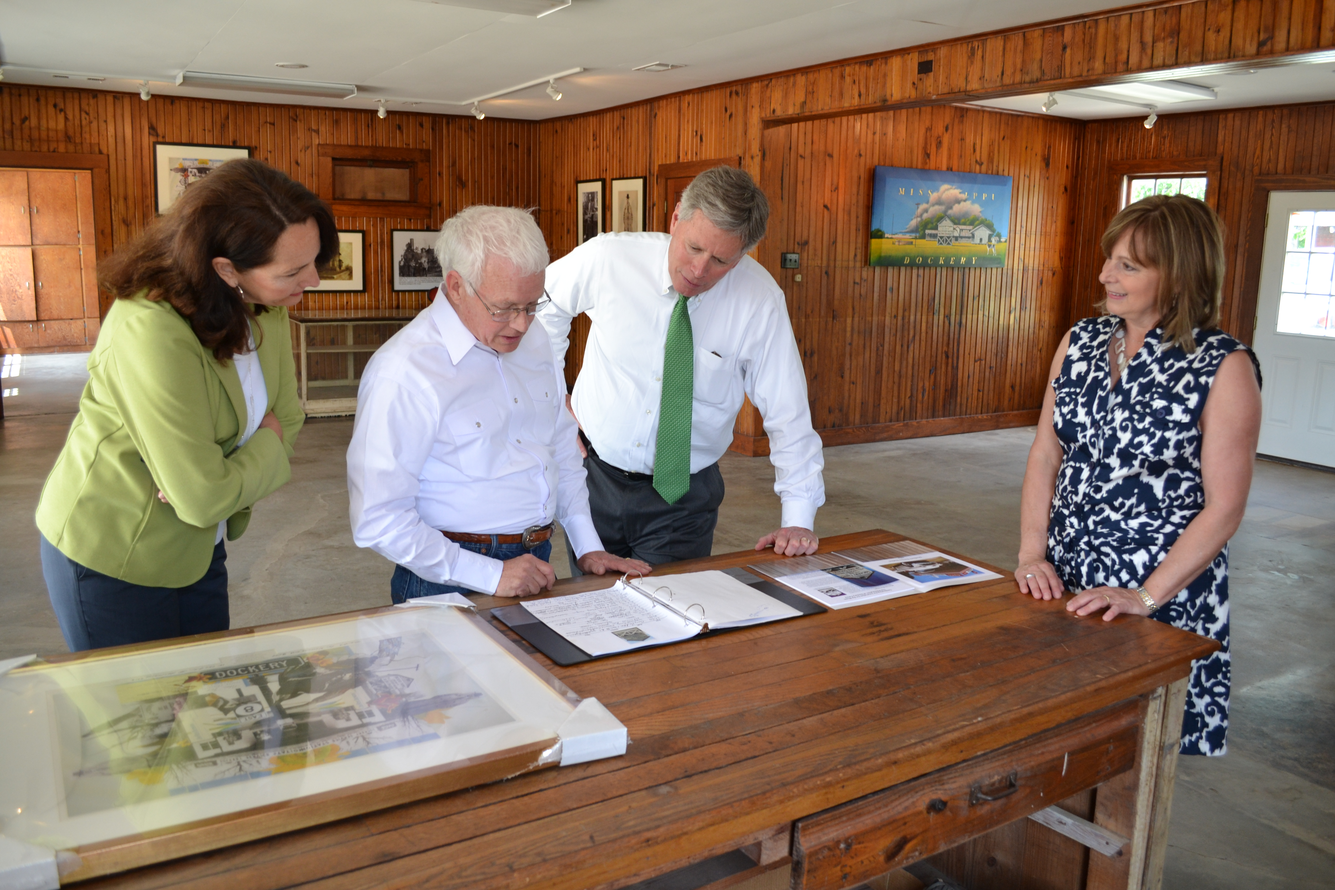 From left, First Lady Nancy LaForge, Delta State Professor Emeritus of Art and Coordinator for the Dockery Farms Foundation Bill Lester, President William N. LaForge and Tennie Lester examine the sign-in book with names of visitors from all over the world who have visited Dockery Farms.