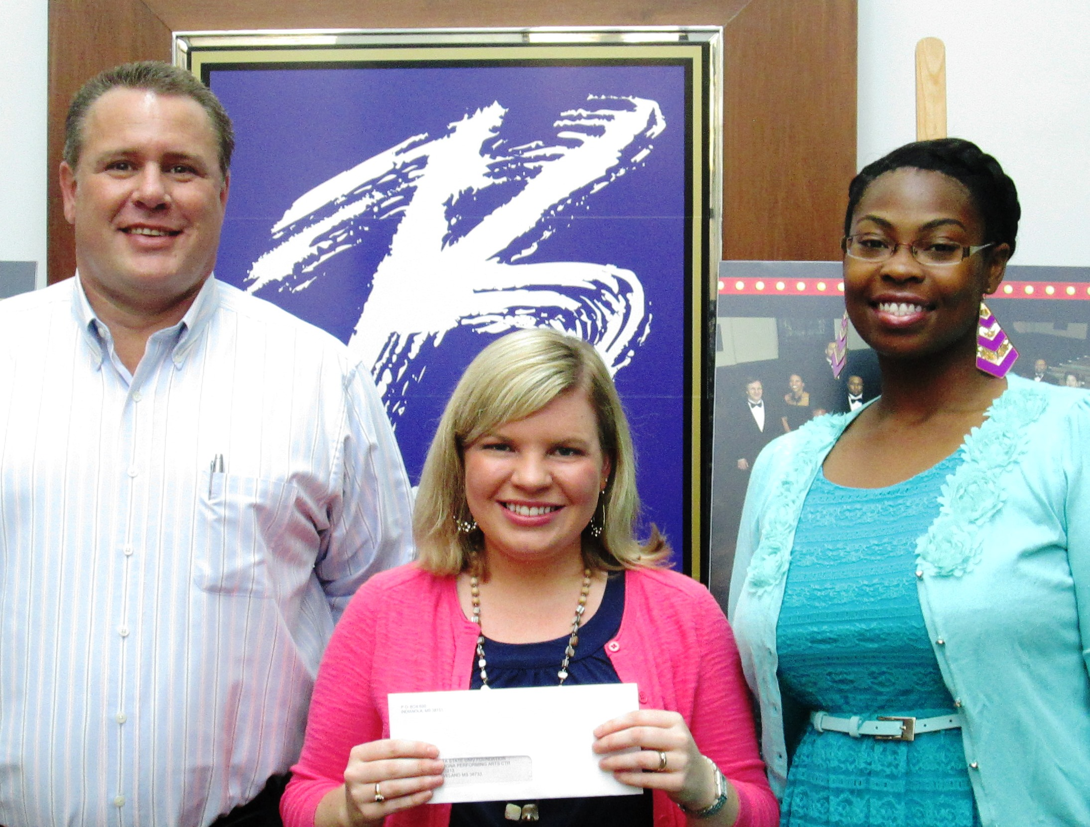 Damon Cranford (left), Director of Marketing, and Curlina Williams (right), Marketing Manager for Double Quick, Inc. present a check for Arts Education Fueled by Double Quick to Whitney Cummins (middle), BPAC Arts Education Coordinator