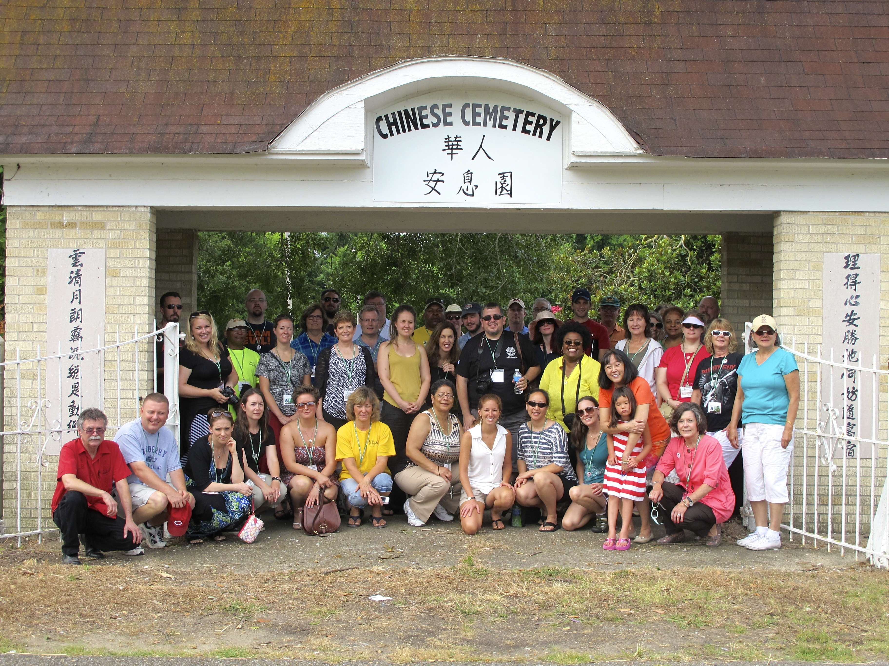 "Participants of the workshop standing in front of the ""New"" Chinese Cemetery in Greenville, where they were introduced to the stories of the Delta Chinese by Cathy Wong. Photo by Rachel Anderson."