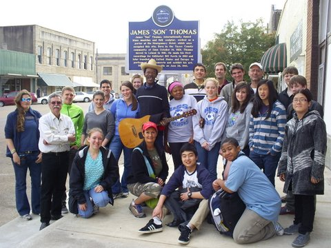"Photo:  Students from the Colorado Springs School in front of the Highway 61 Blues Museum in downtown Leland.  The Mississippi Blues Trail marker celebrates the life of Bluesman James ""Son"" Thomas.  Pat Thomas, James's son, is holding his guitar in front of the marker."
