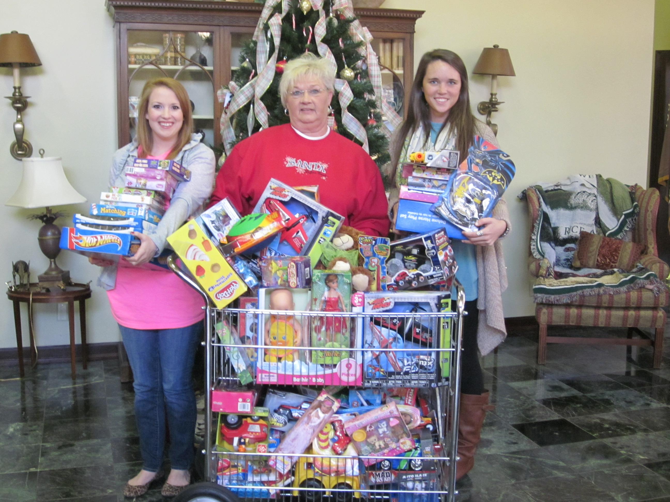 PHOTO:  From left, Amy Scott, Jo Donna Watson, and Shelby McIntire gather the gifts that were donated to the toy drive.