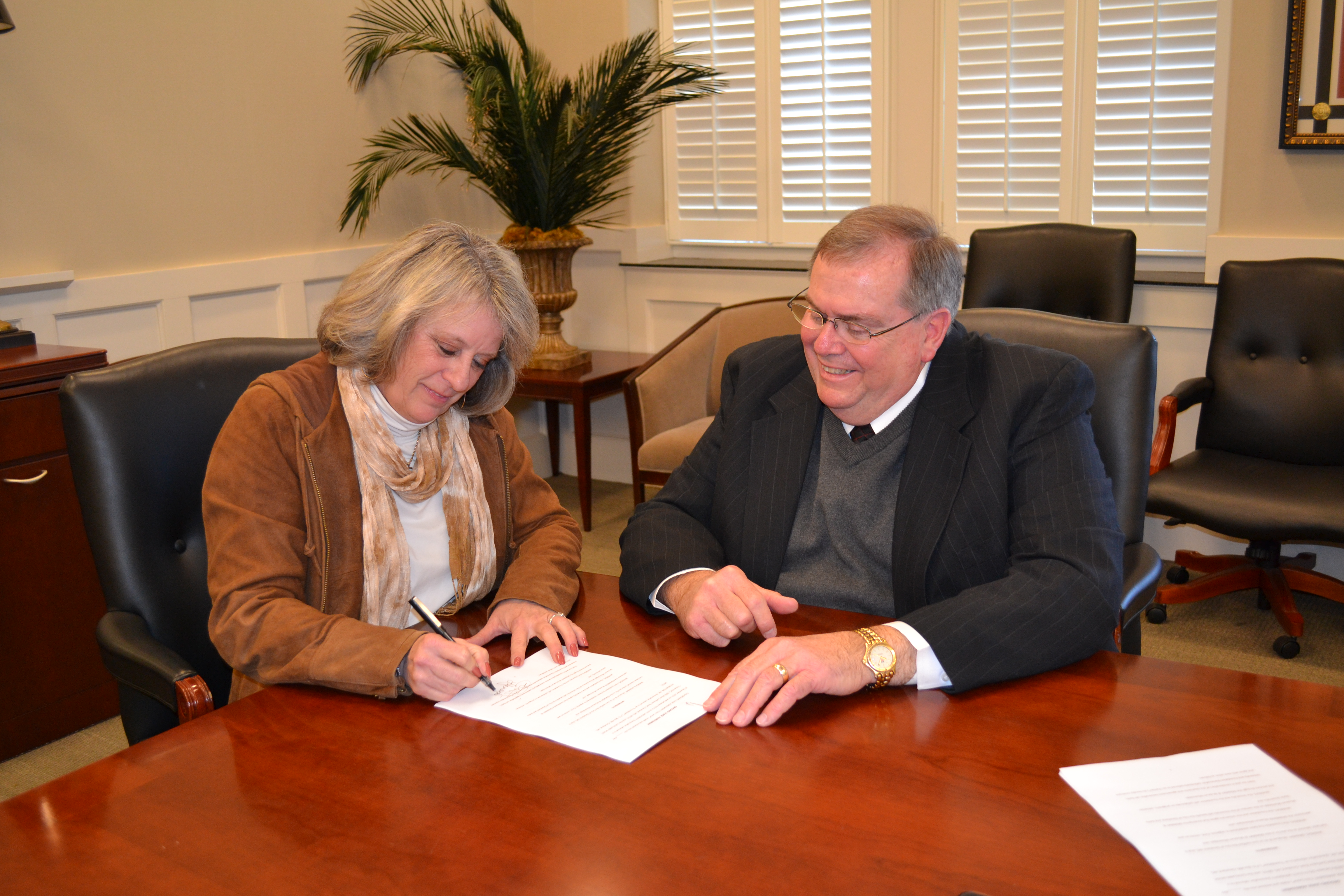PHOTO:  From left, President of the Cleveland Music Foundation Lucy Janoush and Delta State University President Dr. John M. Hilpert sign the lease agreement for the establishment of GRAMMY® Museum Mississippi to be located on the Delta State University campus in Cleveland.