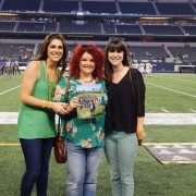 Graduates pose with alumni magazine at ATT stadium