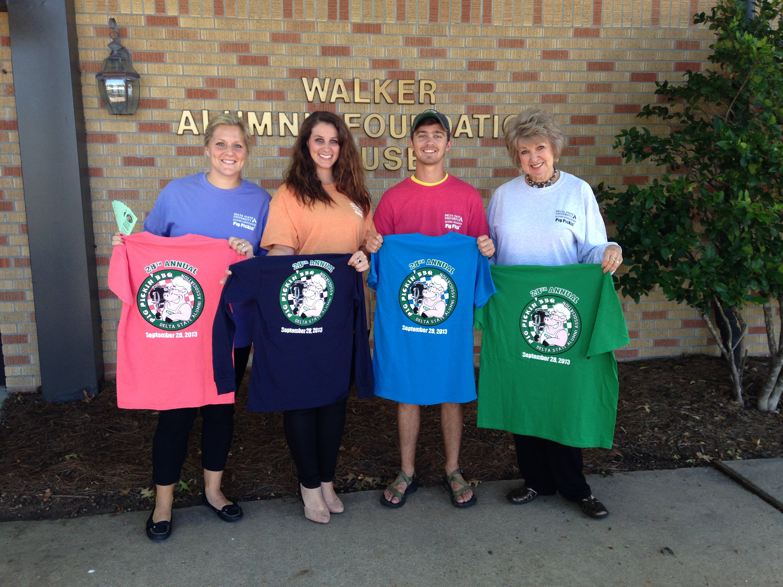 Models holding pig pickin t-shirts
