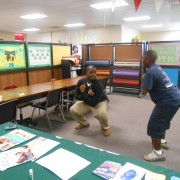 AmeriCorps VISTA member Derrick Price (left) shows a student with asthma an exercise technique during Cleveland School District's Health and Wellness Day at the Cleveland Vocational Tech Complex.
