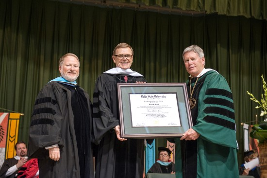 Delta State University Provost Dr. Charles McAdams (left) and President William N. LaForge (right) present UPS CEO David Abney '76 with an honorary doctorate at today's 89th Commencement ceremonies.